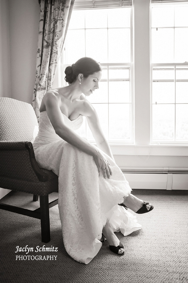 bride sitting in chair putting on high heels