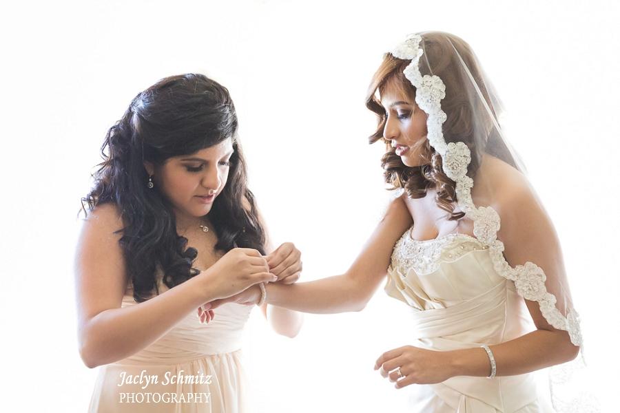 high key bride putting on bracelet