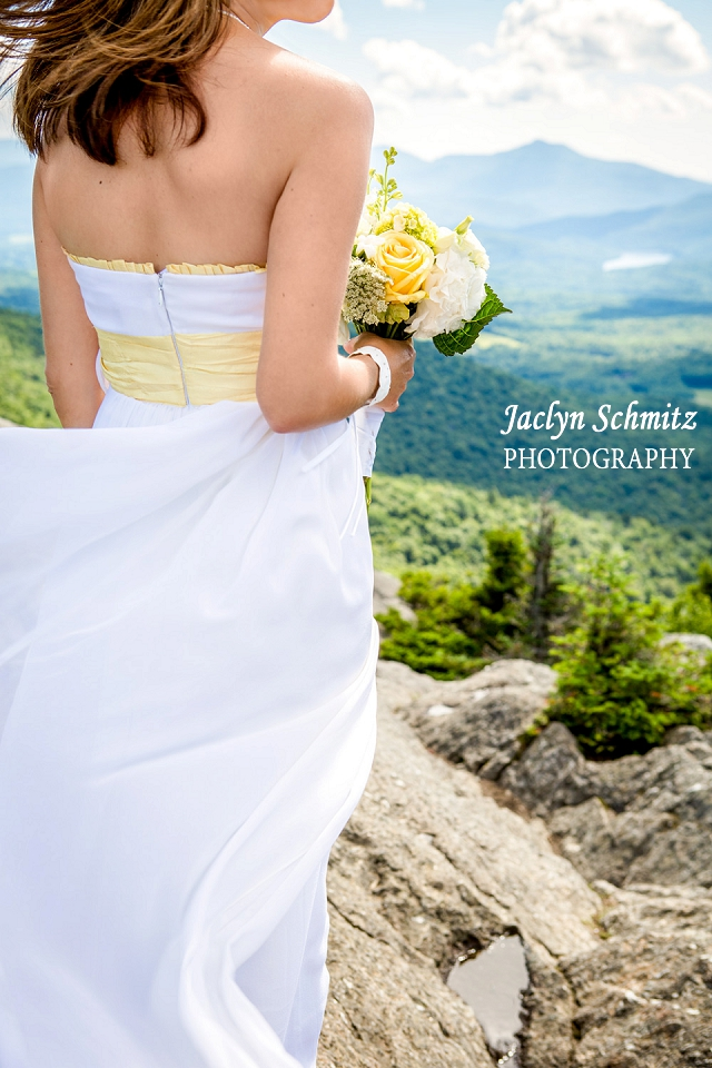 bride's dress blows in the wind as she stands on top of stowe, vt mountain