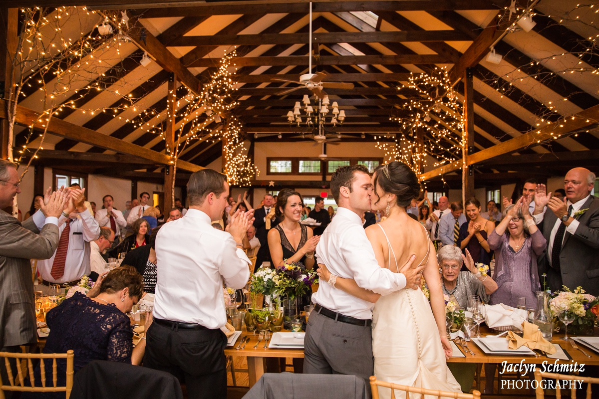 bride and groom kiss as wedding guests clap