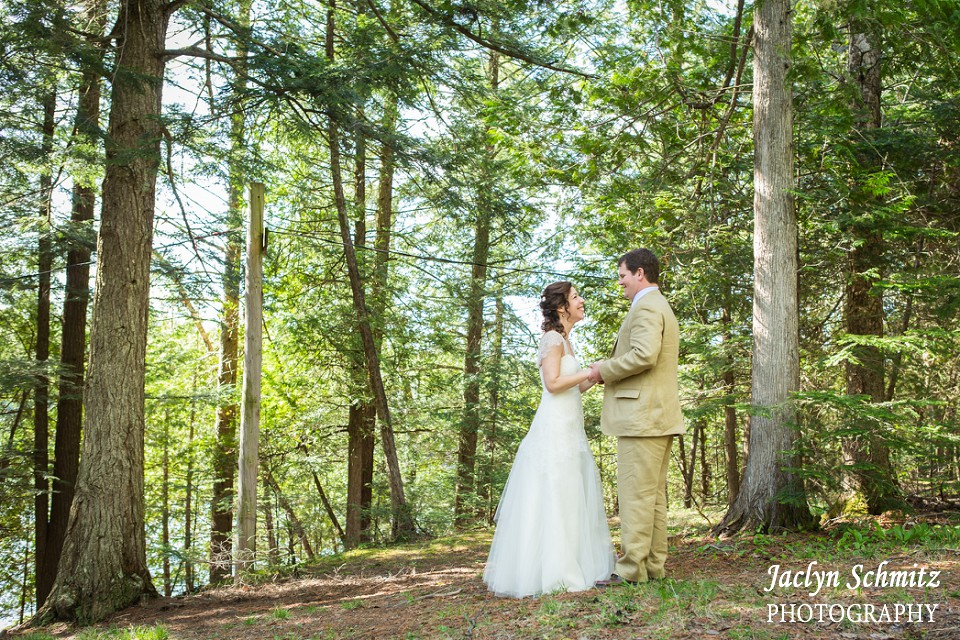 bride laughs with groom among tall forest trees
