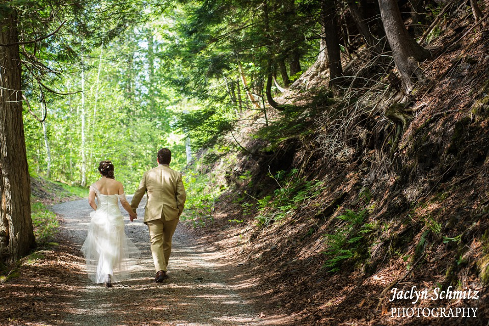 bride and groom walking through secluded forest in vermont