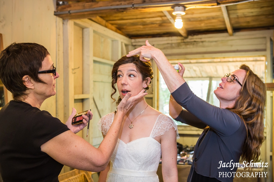bride getting hair and make up simultaneously in cabin