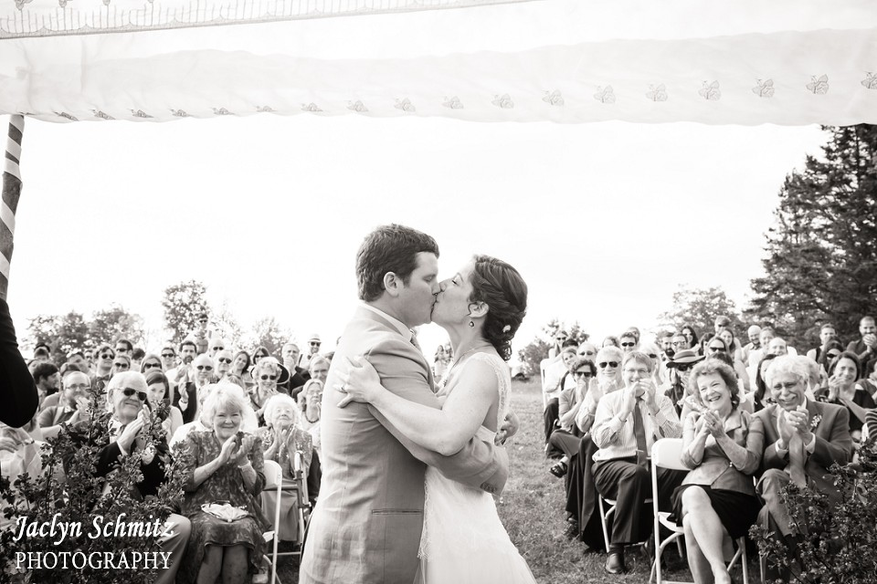 outdoors kiss under chuppah with guests clapping