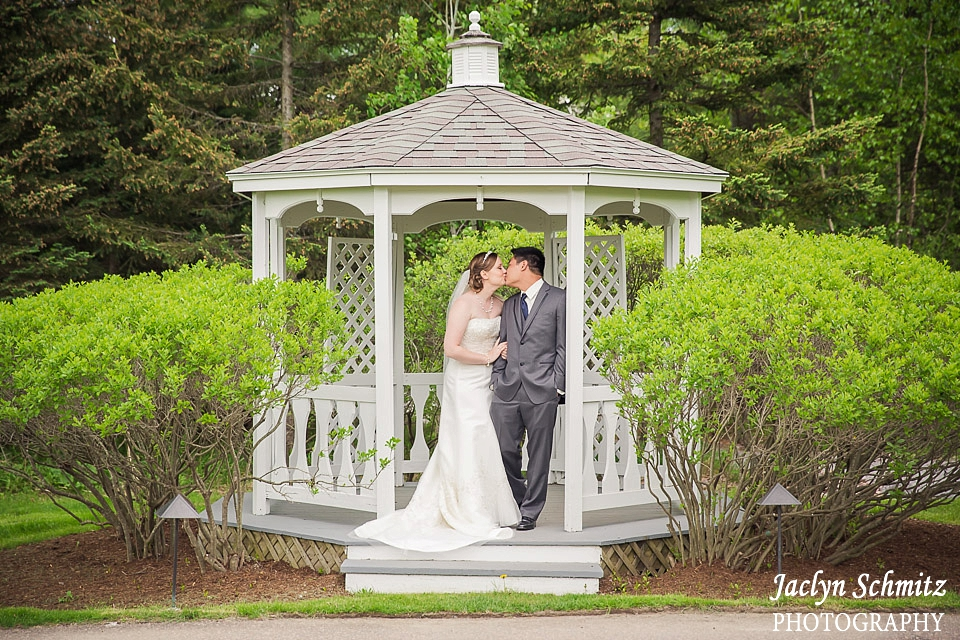 bride and groom kiss inside white gazebo essex vt